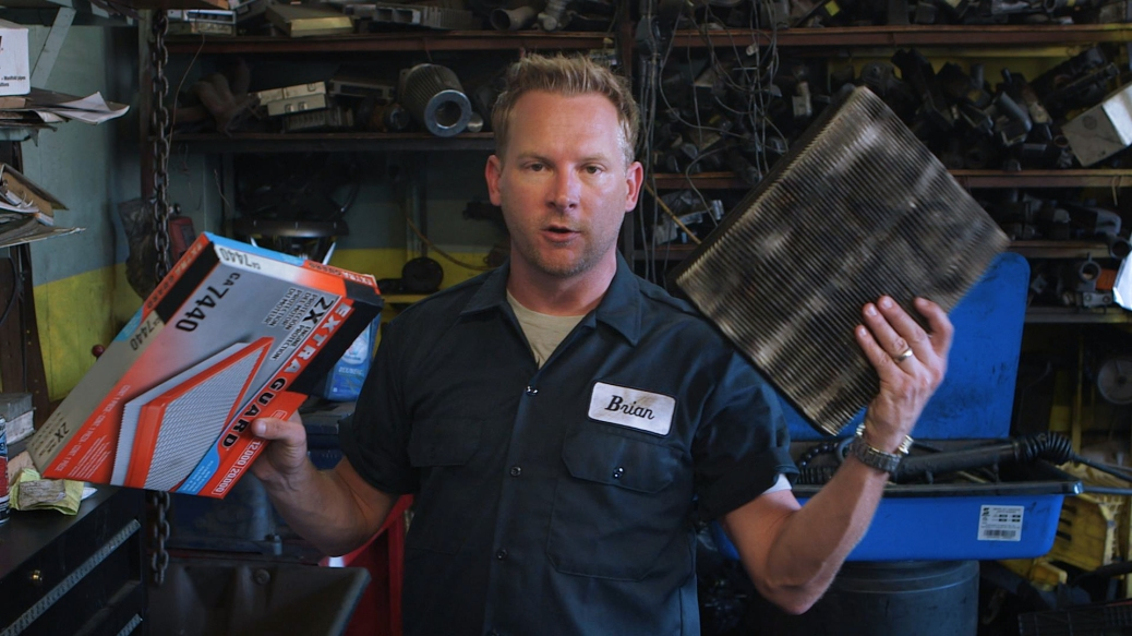 LOS ANGELES- CALIF.- Brian holds up a used car filter and the box of a new car filter. In this scene, he explains how you should ask the mechanic for your old parts in order to make sure the job was done properly.
